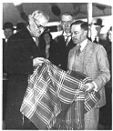 Edward Harrison showing a woven blanket to a visiting dignitary