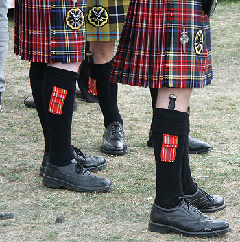 Three kilted figures with brogues.